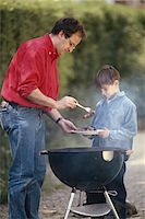 smoked - Father serving cooked food in son's (6-9) plate, outdoors Stock Photo - Premium Royalty-Freenull, Code: 6106-05530317