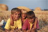Children  (6-9) lying in field, smiling Stock Photo - Premium Royalty-Freenull, Code: 6106-05530502