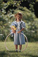 Girl (4-7) holding plastic ring in garden, portrait Stock Photo - Premium Royalty-Freenull, Code: 6106-05530520