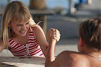 Boy and girl (6-11) arm wrestling Stock Photo - Premium Royalty-Freenull, Code: 6106-05530599
