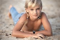 Shirtless girl lying (8-9) on beach, close-up Stock Photo - Premium Royalty-Freenull, Code: 6106-05530695