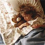Girl (6-7) sleeping with teddy bear on bed, elevated view