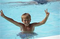 Boy (10-13) showing victory sign in swimming pool, elevated view Stock Photo - Premium Royalty-Freenull, Code: 6106-05531415