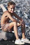 Boy (8-9) sitting on rock at pebbled beach, smiling Stock Photo - Premium Royalty-Freenull, Code: 6106-05531593