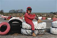 Boy (6-7) sitting on tyre, smiling Stock Photo - Premium Royalty-Freenull, Code: 6106-05531699