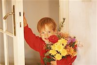 Boy (4-5) at door holding bunch of flowers Stock Photo - Premium Royalty-Freenull, Code: 6106-05531724
