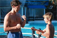 Father and boy (10-13) boxing by poolside Stock Photo - Premium Royalty-Freenull, Code: 6106-05531798