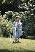 Girl (6-7) playing with plastic hoop in garden Stock Photo - Premium Royalty-Freenull, Code: 6106-05531862