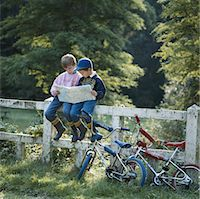 Boys (6-9) sitting on fence looking at map Stock Photo - Premium Royalty-Freenull, Code: 6106-05531944