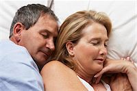 Mature couple lying in bed, eyes closed, close-up Stock Photo - Premium Royalty-Freenull, Code: 6106-05535195