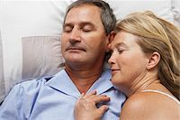 Mature couple lying in bed, eyes closed, close-up Stock Photo - Premium Royalty-Freenull, Code: 6106-05535196
