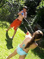 Brother and sister (9-12) having water fight in garden Stock Photo - Premium Royalty-Freenull, Code: 6106-05535315