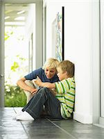 Mother crouching by son (7-9) in hallway Stock Photo - Premium Royalty-Freenull, Code: 6106-05535733