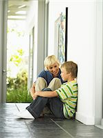 Mother crouching by son (7-9) in hallway, smiling Stock Photo - Premium Royalty-Freenull, Code: 6106-05535734