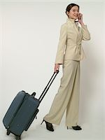 female white background full body - Young businesswoman toting luggage, talking on mobile phone Stock Photo - Premium Royalty-Freenull, Code: 6106-05536373