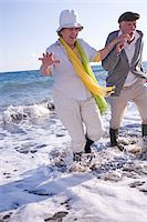 Senior couple running out of sea, smiling Stock Photo - Premium Royalty-Freenull, Code: 6106-05536976
