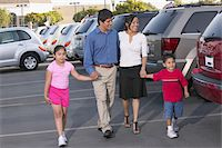 person walking on parking lot - Family walking through car park, holding hands, smiling Stock Photo - Premium Royalty-Freenull, Code: 6106-05537377