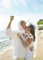 Mature bride and groom kissing on beach under veil, side view Stock Photo - Premium Royalty-Freenull, Code: 6106-05538750