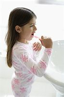 Girl (5-7) leaning on sink, brushing teeth, side view, close-up Stock Photo - Premium Royalty-Freenull, Code: 6106-05539203