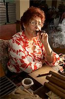 Senior woman smoking cigar in cigar factory, portrait Stock Photo - Premium Royalty-Freenull, Code: 6106-05540162