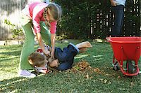 Girl (10-12) play fighting with twin brother in garden Stock Photo - Premium Royalty-Freenull, Code: 6106-05540173