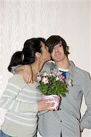 Mother holding gift, kissing teenage son (13-15) on cheek Stock Photo - Premium Royalty-Freenull, Code: 6106-05542086