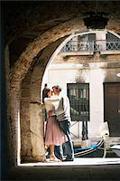 Couple embracing under archway by canal Stock Photo - Premium Royalty-Freenull, Code: 6106-05542465