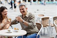 Italy, Venice, couple drinking wine at cafe table, outdoors, smiling Stock Photo - Premium Royalty-Freenull, Code: 6106-05542838