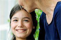 preteen kissing - Grandmother kissing granddaughter (9-11) on forehead, portrait of girl Stock Photo - Premium Royalty-Freenull, Code: 6106-05543136