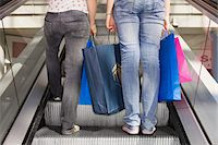 Teenage girls (15-17) on escalator with bags, low section, rear view Stock Photo - Premium Royalty-Freenull, Code: 6106-05543565