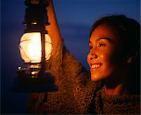 Young woman holding lamp, smiling, outdoors, close-up Stock Photo - Premium Royalty-Freenull, Code: 6106-05543742