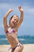 Girl (5-7) playing in water spray on beach, arms raised, eyes closed Stock Photo - Premium Royalty-Freenull, Code: 6106-05545880