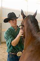 Young man patting American Quarter horse in indoor arena, portrait Stock Photo - Premium Royalty-Freenull, Code: 6106-05545971