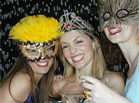Two women wearing masks and tiara, holding drinks, smiling, portrait Stock Photo - Premium Royalty-Freenull, Code: 6106-05547355