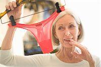 Senior woman holding thong panties in retail store Stock Photo - Premium Royalty-Freenull, Code: 6106-05547582