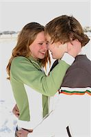 Teenage couple (14-16) embracing in winter landscape, smiling Stock Photo - Premium Royalty-Freenull, Code: 6106-05547633