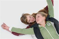 Teenage couple (14-16) holding hands lying in snow, smiling Stock Photo - Premium Royalty-Freenull, Code: 6106-05547635