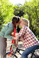Teenage boy and girl (13-15) kissing outdoors on bikes Stock Photo - Premium Royalty-Freenull, Code: 6106-05548087