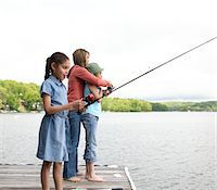 Mother and daughters (8-10) fishing, side view Stock Photo - Premium Royalty-Freenull, Code: 6106-05548301
