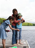 Mother and daughters (8-10) fishing, side view Stock Photo - Premium Royalty-Freenull, Code: 6106-05548302