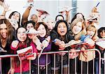 Fans offering notepads for celebrity's signature behind barrier Stock Photo - Premium Royalty-Free, Artist: Blend Images, Code: 635-05550037