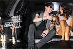 Couple toasting each other in backseat of limo Stock Photo - Premium Royalty-Freenull, Code: 635-05550049