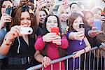 Fans taking pictures with cell phone behind barrier Stock Photo - Premium Royalty-Free, Artist: Blend Images, Code: 635-05550055