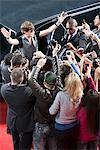 Celebrity emerging from limo towards paparazzi Stock Photo - Premium Royalty-Free, Artist: Blend Images, Code: 635-05550083