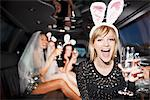 Woman in bunny ears drinking champagne in limo Stock Photo - Premium Royalty-Freenull, Code: 635-05550116