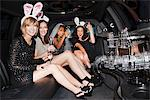 Women in bunny ears drinking champagne in limo Stock Photo - Premium Royalty-Free, Artist: Blend Images, Code: 635-05550132