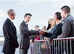 Politician shaking hands with people behind barrier Stock Photo - Premium Royalty-Free, Artist: Blend Images, Code: 635-05550134