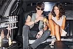 Couple toasting each other in limo Stock Photo - Premium Royalty-Freenull, Code: 635-05550149