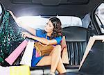 Woman with shopping bags in backseat of limo Stock Photo - Premium Royalty-Freenull, Code: 635-05550158