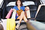 Woman with shopping bags in backseat of limo Stock Photo - Premium Royalty-Freenull, Code: 635-05550166